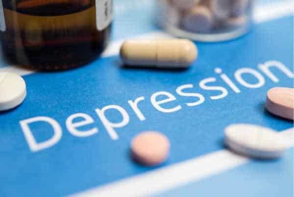 Pills and a blue background with the word depression written on it