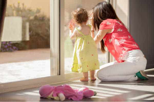 Mom and young daugther peering out the sliding glass doors - homeschooling with depression can make you feel trapped at home and unhappy