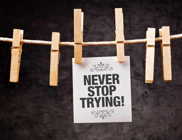 Never Stop Trying motivational message printed on note paper and hanged on clothesline with pins  - when homeschooling with depression never stop trying to find help