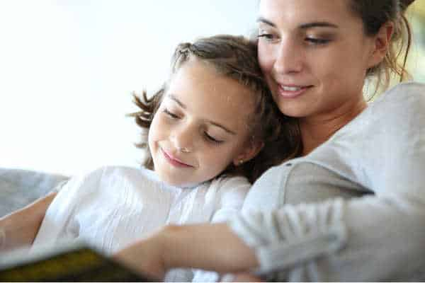 Mom with little girl reading book in sofa, taking a relaxing approach when homeschooling with depression