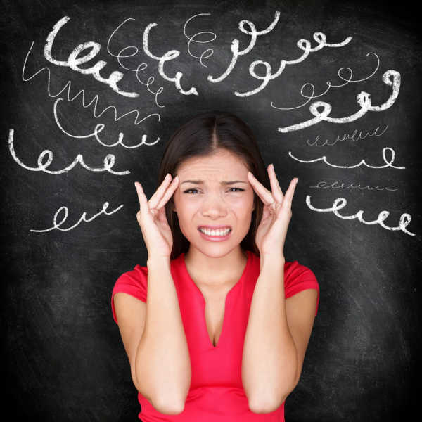 bible verses for homeschool moms should help reduce the stress of this overwhelmed mom.  She has a red short-sleeved shirt on.  Her hands are at her temples and her face looks pained.  Behind her is a blackboard with curlycue lines coming out from her head in a fan.