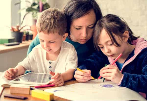 Homeschool mom is seated at a table with her two young children.  Her son is in her lab working on a tablet.  Her daughter is next to her drawing.  The mom is leaning over looking closely at what she is doing.  Homeschooling is more content, just like this picture, with bible verses for homeschool moms.