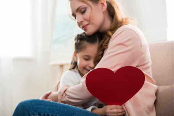Mom sitting on a couch, hugging her daugther.  The daughter is holding a big red heart.  The mom has a serene look on her face - perhaps because she has bible verses for homeschool moms that she meditates on.