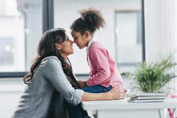 Little girl in a pink sweater and full pony tail sits on a table.  Her mom is sitting on a chair in front of her.  They are both smiling and are touching noses.  It is a picture of love and connection between a child and her homeschool mom.