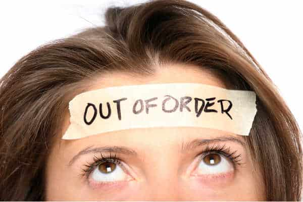Woman with brunette hair and brown eyes.  Picture starts just above her nose.  She is looking up at the masking tape across her forehead that says out of order.  She is illustrating the overwhelmed feeling behind the need for self-care for homeschool moms.