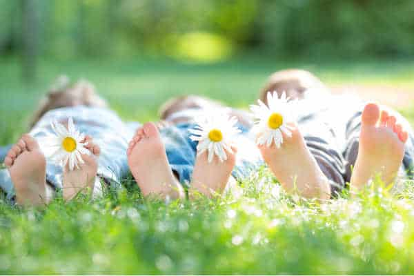 self-care for homeschool moms tip #3 is to send your kids outside.  This is illustrated by three kids laying in the sunshine and the grass.  We see mostly just their feet with each having a daisy stuck between their toes.