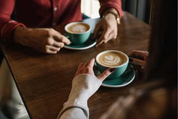 self-care for homeschool moms can look like going on a date - without your kids.  Here we see a mom and dad having coffee together.  We see just the hands and the coffee, green cups with hearts in the froth.