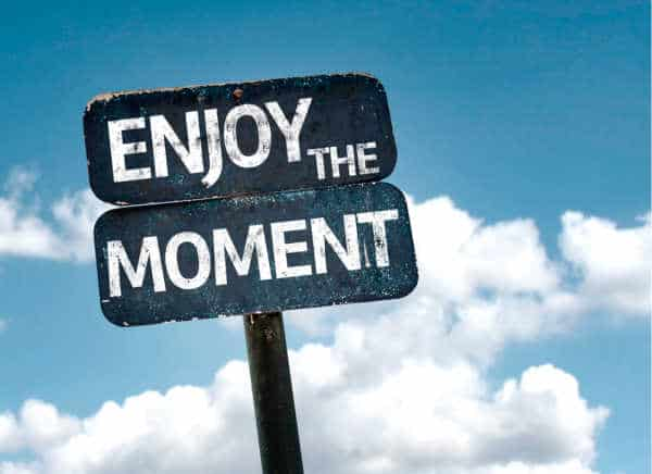 "self-care for homeschool moms can look like just being in the moment. This is illustrated by a street sign that  says ""Enjoy the Moment"" - it is a dark blue and slightly rough around the edge with a metal pole.  The background is a bright blue sky."
