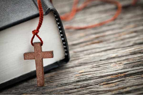 Closeup of wooden Christian cross necklace next to Holy Bible - Having a Bible is an essential to daily devotions.