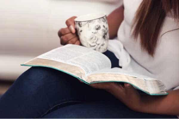 Mom reading her Bible with coffee cup in her hand, she seems like she has all the time in the world and is not wondering how long does my quiet time need to be - very peaceful.