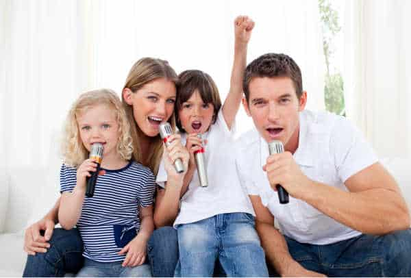 A family of four singing into microphones.  It is funny and ackward which is exactly how some families feel singing at home while trying to get kids to focus for online worship.