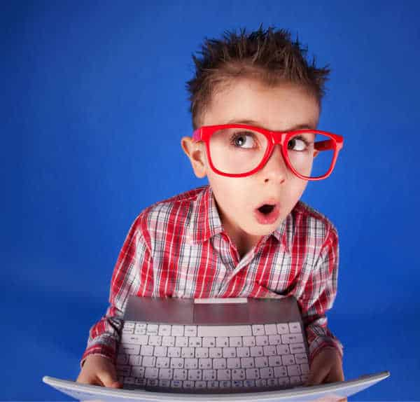 Cute little boy with spiky hair, a plaid shirt, and red oversized glasses. He is holding a computer and has a distracted and suprised look on his face - he exemplifies how hard it is to get kids to focus for online church.