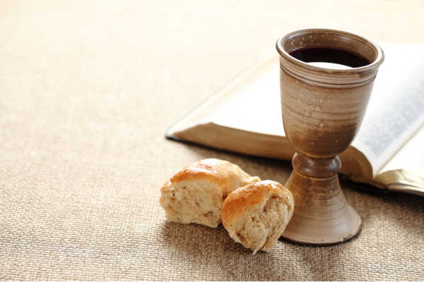 A woven tan colored tablecloth.  Open Bible.  Brown Pottery communion cup filled with dark liquid. A small roll of broken bread.  This is an example of a focial point that would be helpful for creating a worship space at home tha can help kids to focus for online worship.