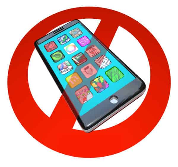 A red No or Stop sign over a smart phone showing apps - it is hard to get kids to focus for online worship if they have their phones. Just say no symbol over a phone.
