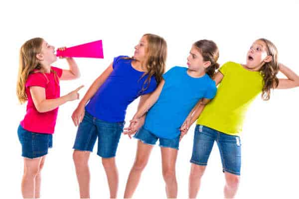 It is hard to parent a bossy child like this one. She has a megaphone and is yellng at three other little girls.  She is the smallest of the group.  They are all wearing jean shorts and then colorful tshirts.