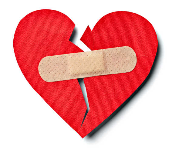 Red paper heart that is cut down the middle a band-aid is trying to bring it back together - this exemplifies the damage that a bossy child can wreck on relationships.