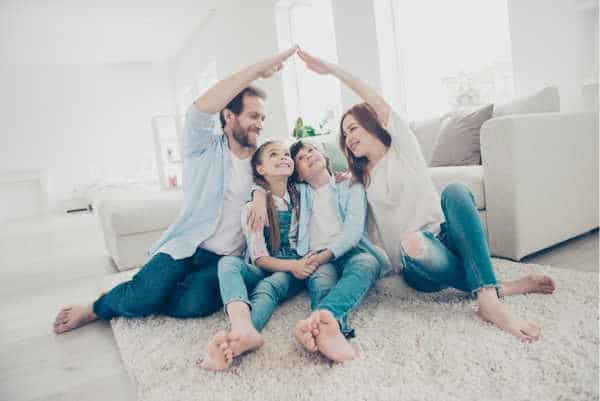 Family of four sitting on the floor in a bright, airy living room.  Mom and Dad have their arms raised over the kids and touching like a roof - when you parent a bossy child you need to give them submission to the authority structure of a family.