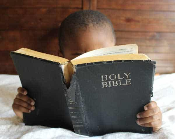Little African-American boy reading a well-worn copy of the Bible.  He face is mostly hidden by it.  He is reading the Bible and wants to memorize the Books of the Bible.