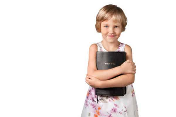 Little blonde haired girl with a pixie cut and dressed in a sleeveless white floral dress is squeezing a black Bible in front of her in a hug.  She is excited because is working hard to memorize the Books of the Bible.