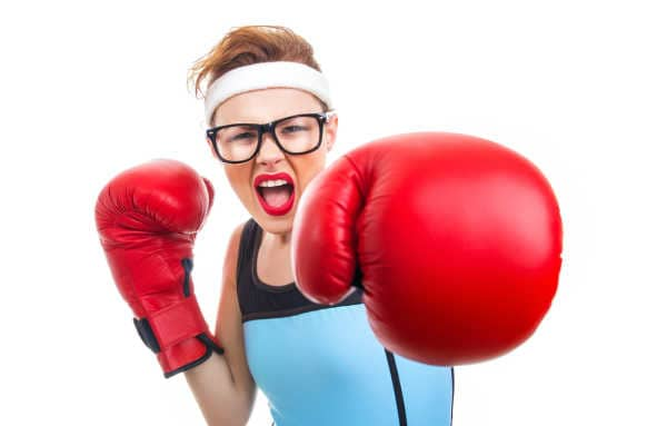 Funny woman with red lipstick, black glasses, and red boxing gloves - she is beating back mom guilt.