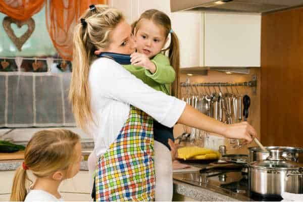 Mom overwhelmed holding a child while talking on the phone and trying to cook supper.  Modern life is so busy, family should consider the peace of the family business model as a reason to raise kids to be entrepreneurs.