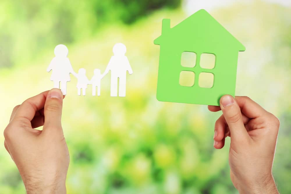 Female hands holding paper house and family on green blurred background reason why to raise kids to be entrepreneurs; entrepreneur vs employee mindset