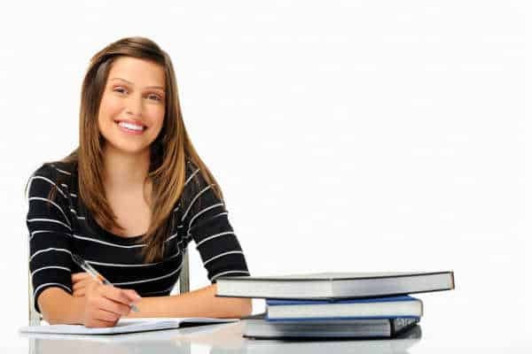 Happy young woman in a black and white stripped shirt studying and learning how to - prepare your homeschoooler to be an entreprenuer