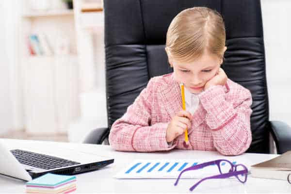 Little girl in a pink tweed suit sitting at an office desk looking at paperwork.  She is a budding entreprenuer - prepare your homeschooler to be an entreprenuer