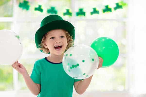 Young boy celebrating St Patrick's Day with green balloons and a garland of clover.  Perhaps he is learning about this Christian saint at church.