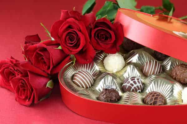 Heart-shaped box of chocolate truffles with red roses.  Traditional gifts for St. Valentine's Day.