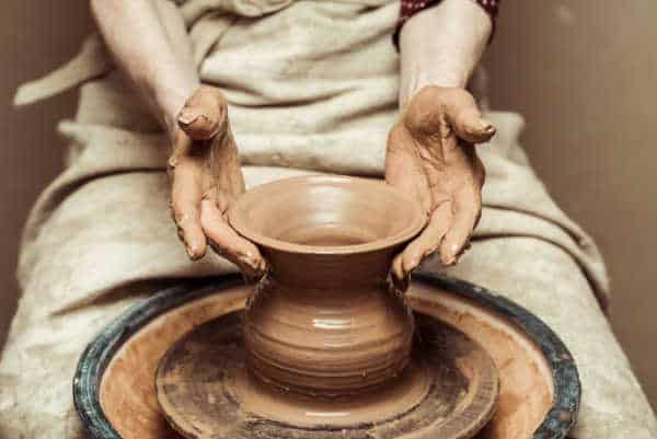 Close up of female hands working on potters wheel just like the making of pottery in the Bible.