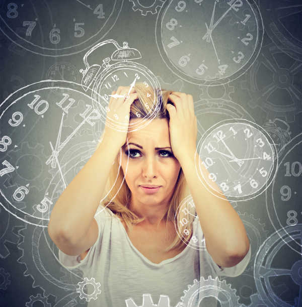 Woman in white top gripping her head.  She longs to simpify your family life with clocks spinning all around her head.