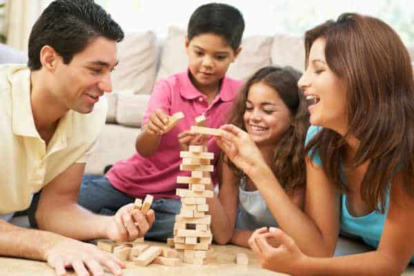 Family in their living room playing Jenga, when you simplify your family life there is time to play games.