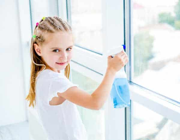 Little girl in a white blouse cleaning a window with blue cleaner on behalf of an unappreciated mom