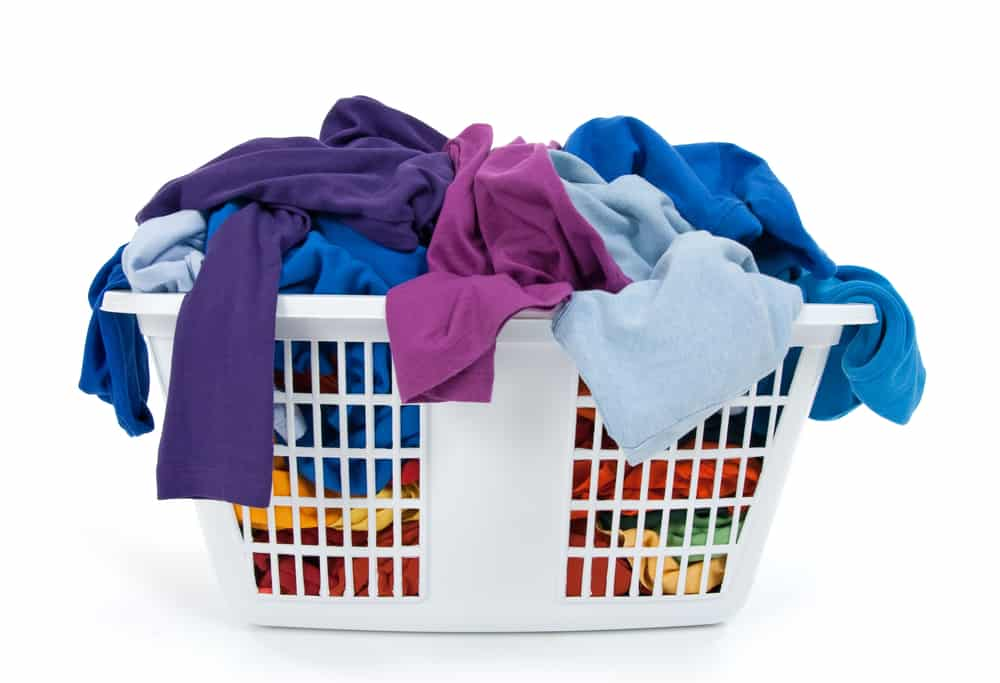 Colorful clothes in a laundry basket on white background. Blue, indigo, purple that needs to be folded by an unappreciated mom.